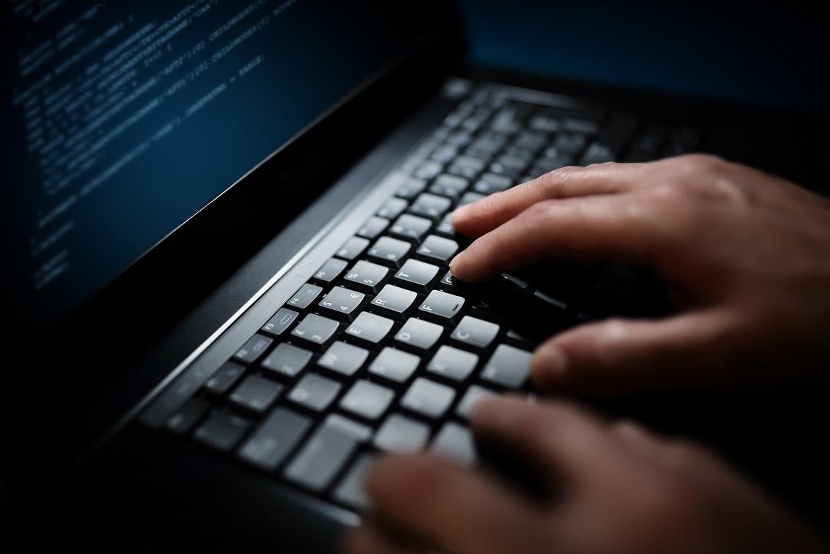 Programmer or computer hacker typing code on laptop keyboard