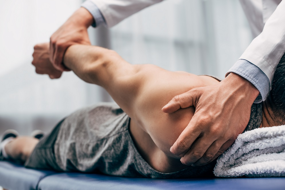 selective focus of chiropractor stretching arm of patient in hospital